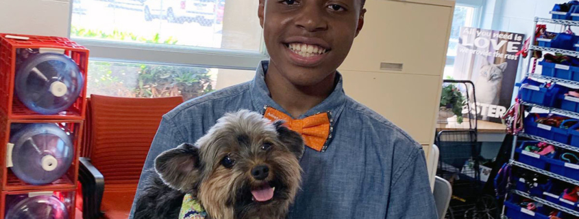 this photo shows Darius Brown with a dog wearing one of his bowties