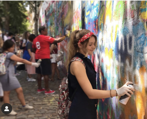 this photo shows Bella Almeida spraypainting the Earthy Creations logo on a wall in Prague