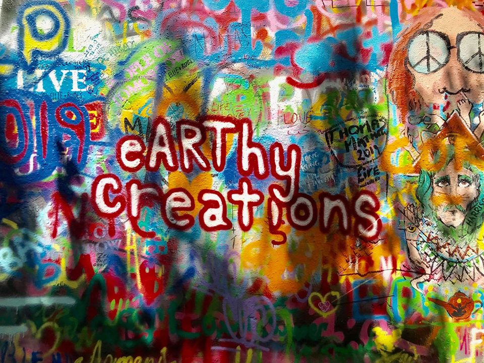 this photo shows the eyecatching earthy creations logo at the John Lennon Wall