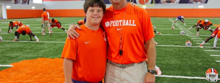 this photo shows Dabo Swinney, a major supporter of the Shepherd Hotel, with a person with special needs.