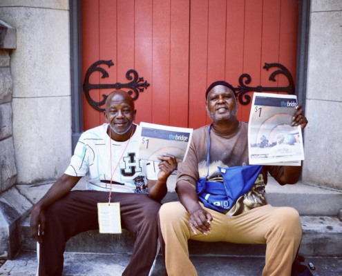 this photo depicts two men holding up a copy of the Memphis street newspaper, The Bridge