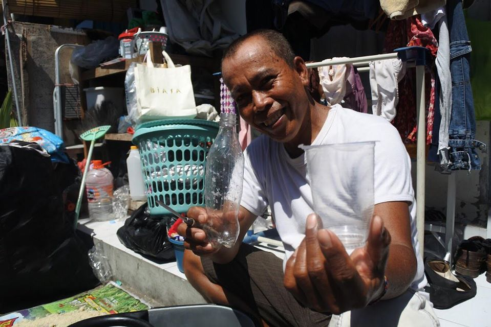 this is a photo of a man sorting through plastic waste for the Plastic Bank