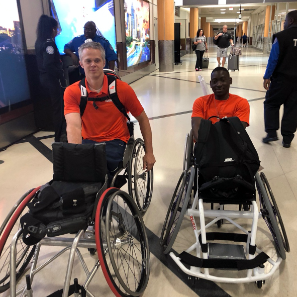 this photo shows tennis wheelchair athletes Jeff Townsend and Marsden Miller of Clemson University trying to navigate an escalator with four wheelchairs