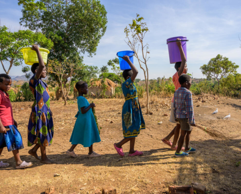this photo shows women and children in Zambia walking a long distance for clean water