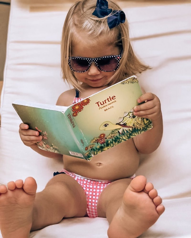 photo of a small child reading a Papinee book that ties into the company's children's programming for YouTube during the pandemic