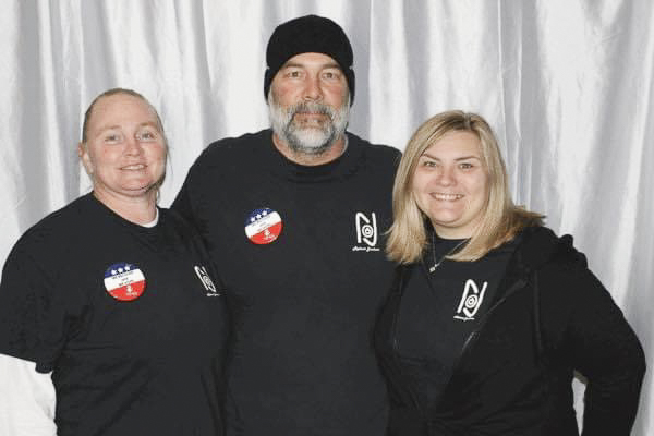 photo of jennifer langston of Reboot Jackson with colleagues in black logoed shirts