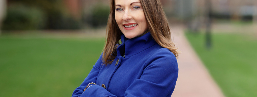 this is a photo of Dr. Michele Speitz of Furman University with arms crossed, wearing a royal-blue outfit