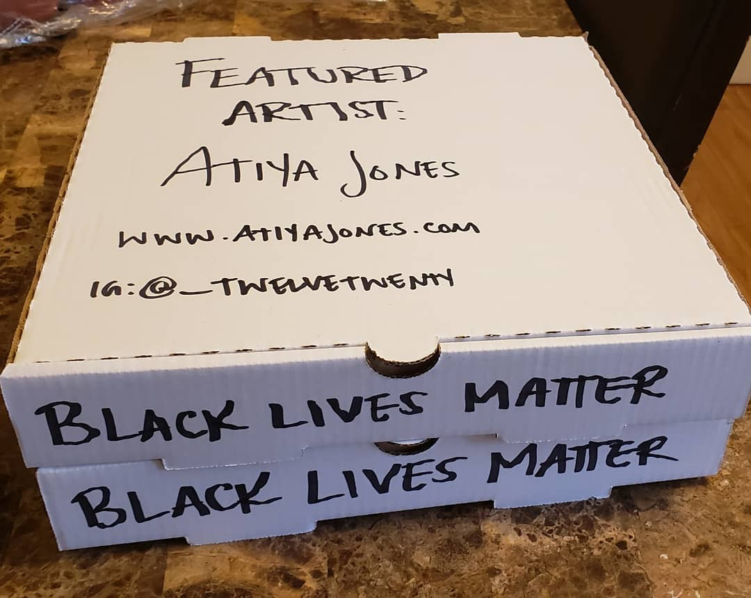 this photo shows a pizza box promoting artist Atiya Jones for the Social Justice Pizza Project