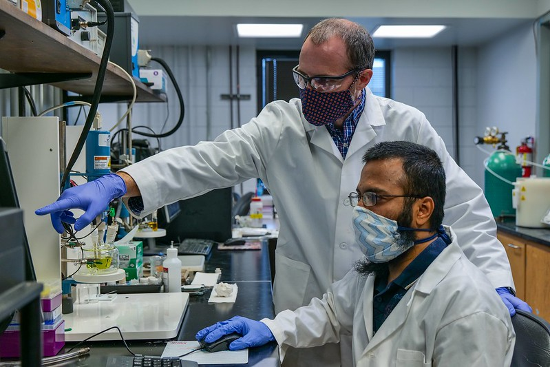 Byron Farnum and a member of his solar energy research team perform an experiment in the lab.