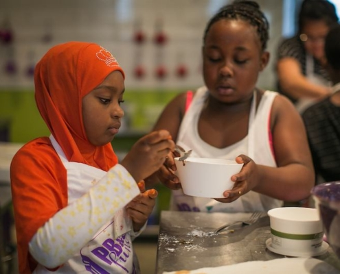 this photo shows two children preparing food for the needy at the PB&J Fund.