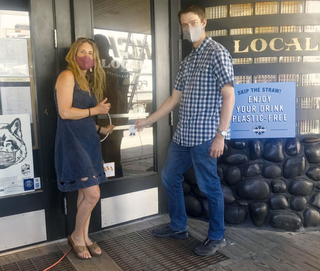 julie deardorff and josh hirschmann of Local Restaurant and Bar pose in front of the restaurant's door where a plastic-free sticker has been placed.