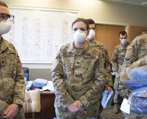 this photo shows Lincoln Memorial University veterinary medicine student Victoria Orlando in her National Guard uniform wearing a protective mask at a nursing facility