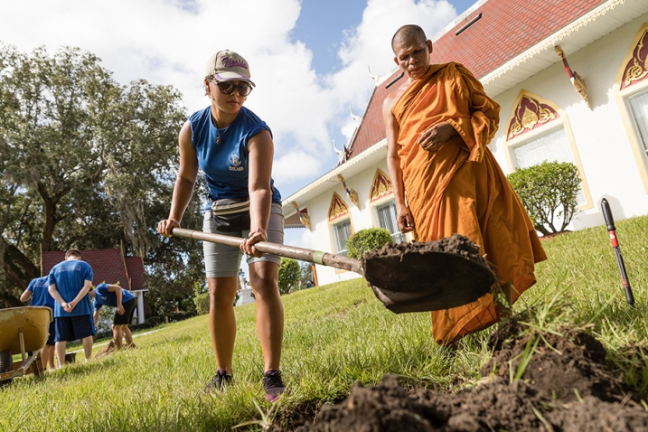 a Rollins College student digs a hole at a Buddhist temple while a monk watches on during a SPARC Day community service event