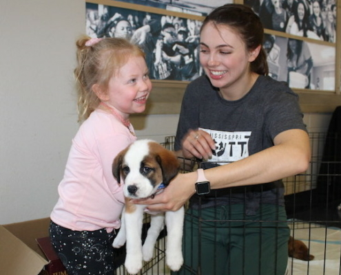 this photo shows Neely Griggs, 2020 recipient of the Algernon Sydney Sullivan Award and an animal welfare advocate, handing a puppy to a little girl at Mississippi Mutts in Oxford, Mississippi.