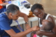 this photo shows Auburn University's Valarie Thomas performing a medical checkup on a baby in Ghana as part of the Ghana Healthcare Program.
