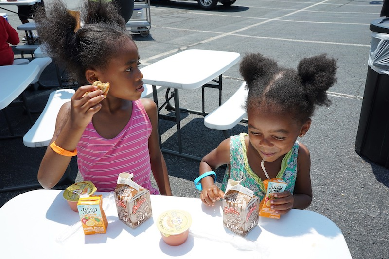 this photo shows two adorable little black girls enjoying a free meal from No Kid Hungry