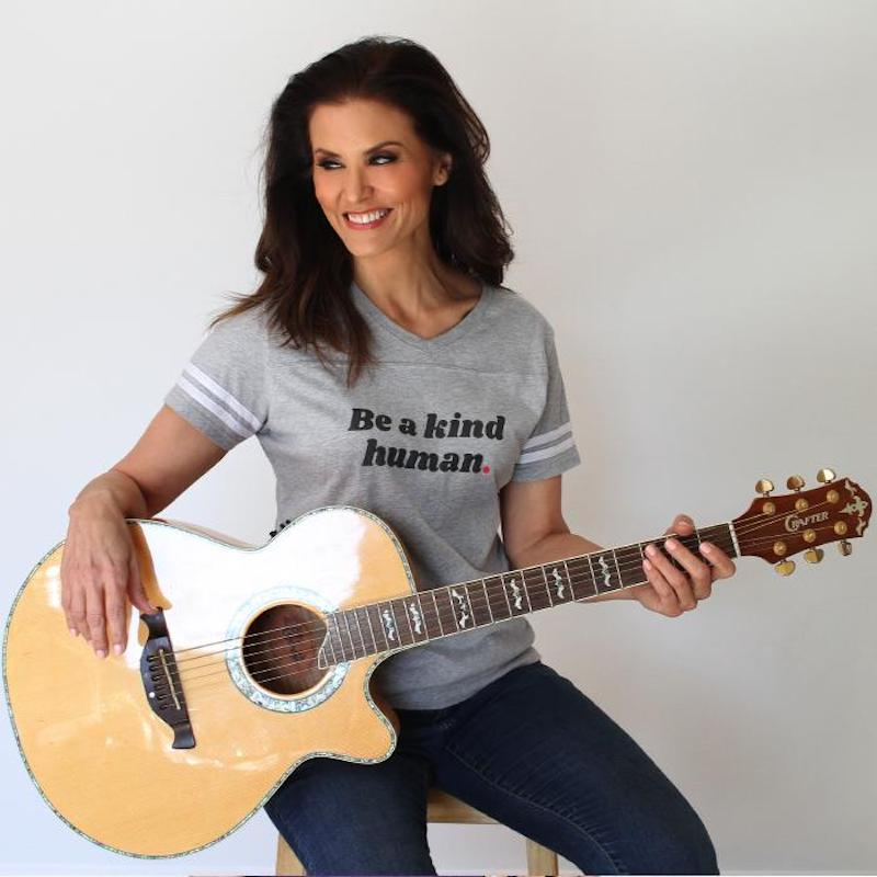 this photo shows former Miss USA Lu Parker wearing a t-shirt from Be Kind & Co. and holding an acoustic guitar