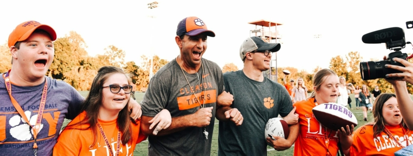 This photo shows Clemson Head Football Coach Dabo Swinney leading a group of young people with intellectual disabilities onto the field before a football game.