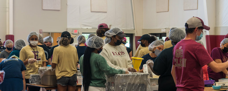 this photo shows student volunteers at Elon University packing meals for Rise Against Hunger