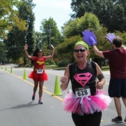 this photo shows three participants dressed in superhero costumes for the Great Cape Race hosted by Elon University