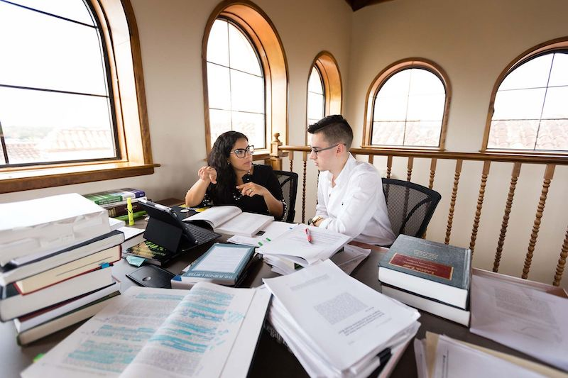 this photo shows Rollins College professor Josie Balzac-Arroyo working one-on-one with a student