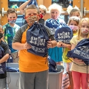this photo shows a group of children receiving shoes from Shoes 4 the Soul at the University of the Cumberlands
